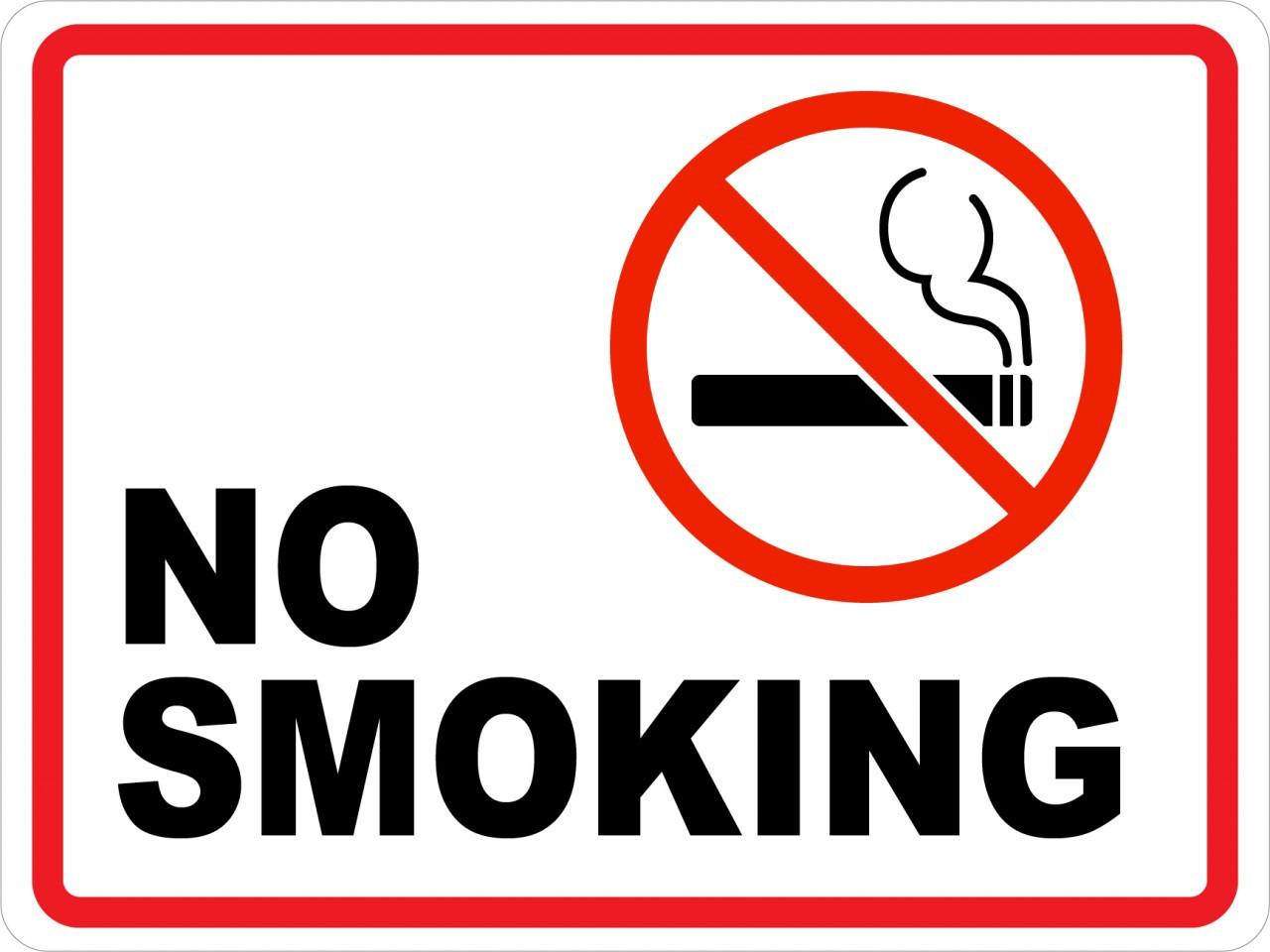 Joaquin Phoenix smokes underneath a No Smoking sign