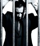 14715278-very-good-looking-office-manager-dressed-in-a-nice-suit-is-in-jail-behind-prison-bars